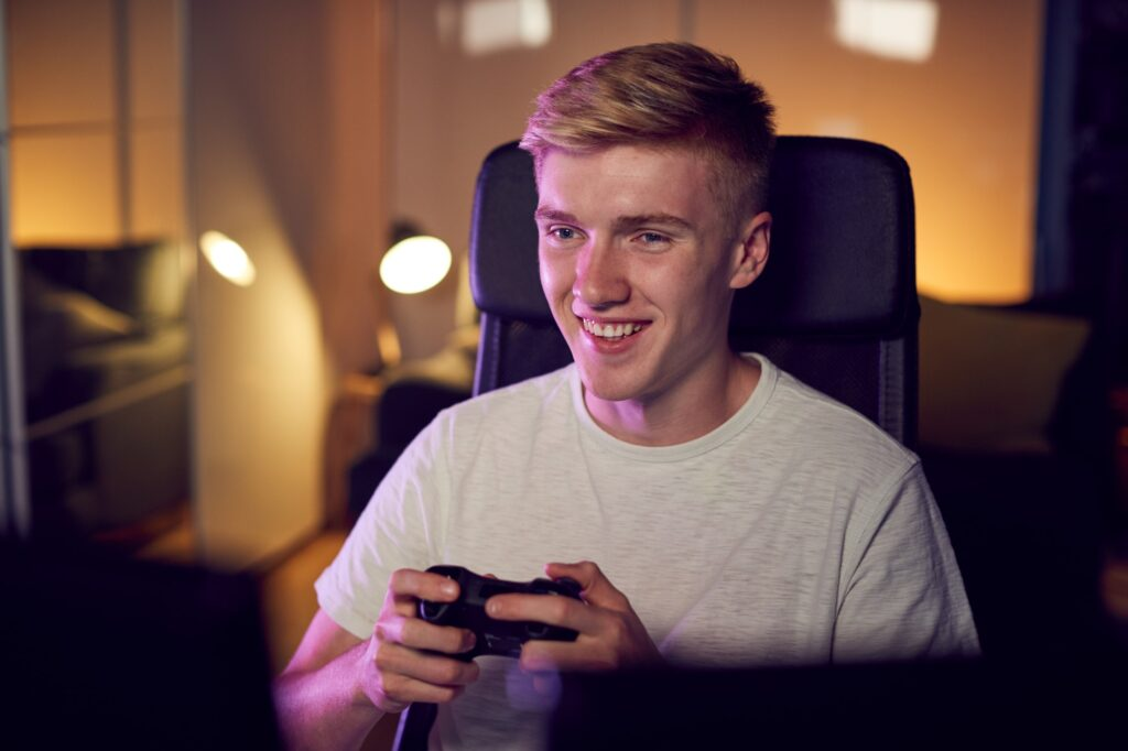 Teenage Boy With Game Pad Sitting In Chair and Gaming At Home